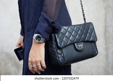 MILAN, ITALY - SEPTEMBER 20, 2018: Woman with black Chanel leather bag and Rolex Datejust watch with black dial before Max Mara fashion show, Milan Fashion Week street style