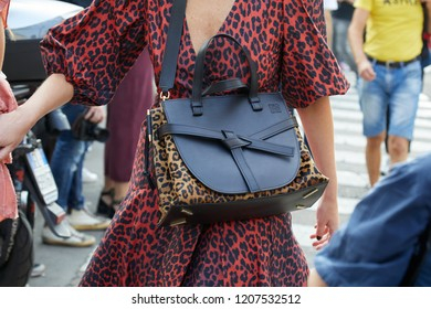 MILAN, ITALY - SEPTEMBER 20, 2018: Woman with black leather and leopard skin pattern Loewe bag before Max Mara fashion show, Milan Fashion Week street style