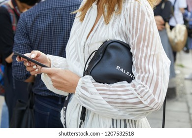 MILAN, ITALY - SEPTEMBER 20, 2018: Woman with black leather Balenciaga bag and white striped shirt looking at smartphone before Max Mara fashion show, Milan Fashion Week street style