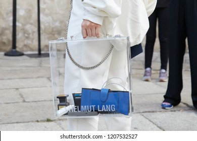 MILAN, ITALY - SEPTEMBER 20, 2018: Man in white with transparent Helmut Lang bag and blue wallet before Max Mara fashion show, Milan Fashion Week street style