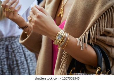 MILAN, ITALY - SEPTEMBER 20, 2018: Woman with golden Cartier watch and bracelets before Max Mara fashion show, Milan Fashion Week street style