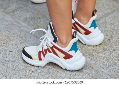 MILAN, ITALY - SEPTEMBER 20, 2018: Woman with Louis Vuitton white, red, blue and yellow sneakers before Max Mara fashion show, Milan Fashion Week street style