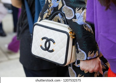 MILAN, ITALY - SEPTEMBER 20, 2018: Woman with black and white Chanel leather bag and jacket with parrots design before Genny fashion show, Milan Fashion Week street style