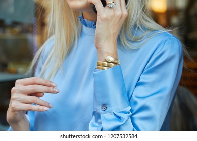 MILAN, ITALY - SEPTEMBER 20, 2018: Woman with golden Movado snake watch and blue satin shirt before Vivetta fashion show, Milan Fashion Week street style