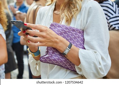 MILAN, ITALY - SEPTEMBER 20, 2018: Woman with purple Goyard bag and Jaeger Lecoultre watch looking at smartphone before Max Mara fashion show, Milan Fashion Week street style