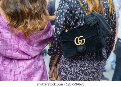 MILAN, ITALY - SEPTEMBER 20, 2018: Woman with black velvet Gucci bag and dress with purple floral design before Genny fashion show, Milan Fashion Week street style