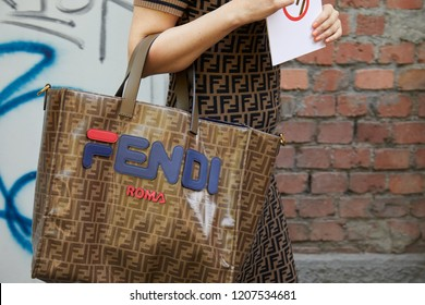 MILAN, ITALY - SEPTEMBER 20, 2018: Woman with brown Fendi bag and dress before Fendi fashion show, Milan Fashion Week street style
