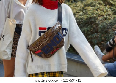 MILAN, ITALY - SEPTEMBER 20, 2018: Woman with Fendi white and red turtleneck and pouch before Fendi fashion show, Milan Fashion Week street style