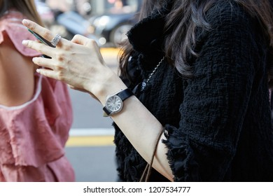 MILAN, ITALY - SEPTEMBER 20, 2018: Woman with black jacket and watch and ring with diamonds looking at smartphone before Max Mara fashion show, Milan Fashion Week street style