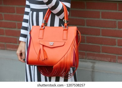 MILAN, ITALY - SEPTEMBER 20, 2018: Woman with orange leather bag and black and white striped dress before Fendi fashion show, Milan Fashion Week street style