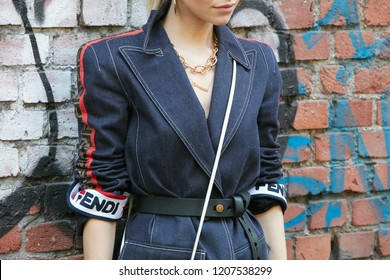 MILAN, ITALY - SEPTEMBER 20, 2018: Woman with blue denim Fendi dress and golden necklace before Fendi fashion show, Milan Fashion Week street style