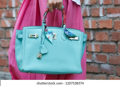 MILAN, ITALY - SEPTEMBER 20, 2018: Woman with Hermes turquoise leather bag and pink dress before Fendi fashion show, Milan Fashion Week street style