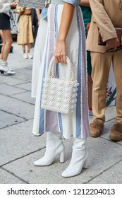 MILAN, ITALY - SEPTEMBER 20, 2018: Woman with white pearls bag striped skirt leather boots before Max Mara fashion show, Milan Fashion Week street style