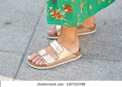 MILAN, ITALY - SEPTEMBER 21, 2018: Woman with golden Birkenstock sandals and green floral dress before Blumarine fashion show, Milan Fashion Week street style