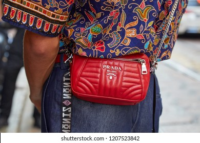 MILAN, ITALY - SEPTEMBER 21, 2018: Man with red leather Prada bag and floral blue shirt before Iceberg fashion show, Milan Fashion Week street style