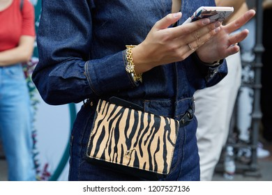 MILAN, ITALY - SEPTEMBER 21, 2018: Woman with blue denim overalls, golden bracelets and giraffe leather bag looking at smartphone before Sportmax fashion show, Milan Fashion Week street style