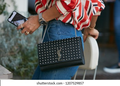 MILAN, ITALY - SEPTEMBER 21, 2018: Woman with black Yves Saint Laurent black leather bag with studs before Tods fashion show, Milan Fashion Week street style