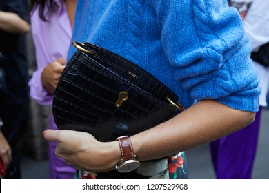 MILAN, ITALY - SEPTEMBER 21, 2018: Woman with black reptile leather Bally bag and blue sweater before Sportmax fashion show, Milan Fashion Week street style