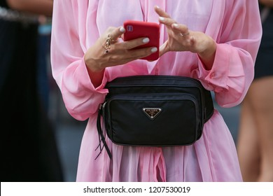 MILAN, ITALY - SEPTEMBER 21, 2018: Woman with pink dress and black Prada pouch before Marco de Vincenzo fashion show, Milan Fashion Week street style