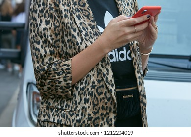 MILAN, ITALY - SEPTEMBER 21, 2018: Woman with leopard pattern jacket and black Adidas shirt looking at smartphone with red cover before Marco de Vincenzo fashion show, Milan Fashion Week street style