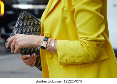 MILAN, ITALY - SEPTEMBER 21, 2018: Woman with yellow jacket, Cartier watch and gray Dior bag before Sportmax fashion show, Milan Fashion Week street style