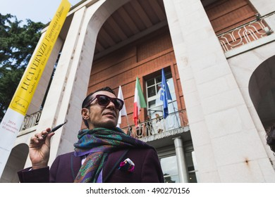 MILAN, ITALY - SEPTEMBER 22, 2016: Fashionable man poses outside Pucci fashion show building during Milan Women Fashion Week SS17.
