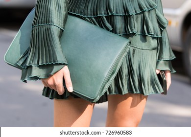 Milan, Italy - September 22, 2017: Model wearing green plisset dress and a big green pochette bag during Armani's parade, photographed on the street