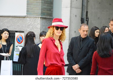 MILAN, ITALY - SEPTEMBER 22, 2017: woman poses in street for photographers in red dress before ARMANI fashion show at Milan Woman Fashion Week