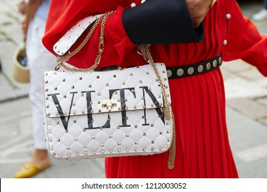 MILAN, ITALY - SEPTEMBER 22, 2018: Woman with white Valentino bag with golden studs and red dress before Philosophy fashion show, Milan Fashion Week street style