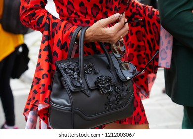 MILAN, ITALY - SEPTEMBER 22, 2018: Woman with black leather Versace bag and red leopard skin Versace bag before Philosophy fashion show, Milan Fashion Week street style