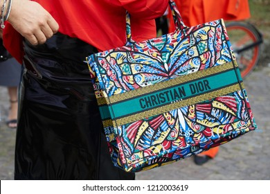 MILAN, ITALY - SEPTEMBER 22, 2018: Woman with Christian Dior colorful bag and red shirt before Philosophy fashion show, Milan Fashion Week street style