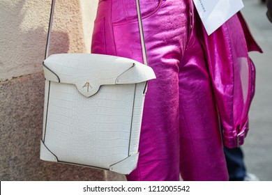 MILAN, ITALY - SEPTEMBER 22, 2018: Woman with white crocodile leather bag and pink metallic trousers before Ermanno Scervino fashion show, Milan Fashion Week street style