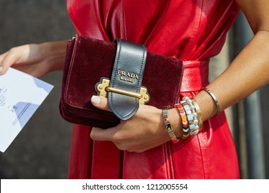 MILAN, ITALY - SEPTEMBER 22, 2018: Woman with red velvet bag and red leather dress before Ermanno Scervino fashion show, Milan Fashion Week street style