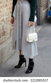MILAN, ITALY - SEPTEMBER 22, 2018: Woman with white Chanel leather bag and gray shirt before Ermanno Scervino fashion show, Milan Fashion Week street style