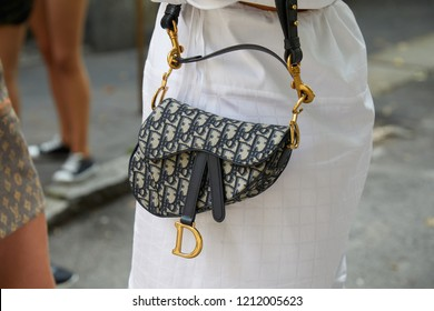 MILAN, ITALY - SEPTEMBER 22, 2018: Woman with Dior bag and white dress before Simonetta Ravizza fashion show, Milan Fashion Week street style