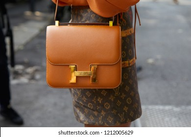MILAN, ITALY - SEPTEMBER 22, 2018: Woman with brown leather Hermes bag and Louis Vuitton skirt before Simonetta Ravizza fashion show, Milan Fashion Week street style