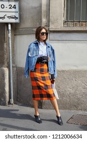 MILAN, ITALY - SEPTEMBER 22, 2018: Woman with orange and black checkered skirt and blue denim jacket before Ermanno Scervino fashion show, Milan Fashion Week street style