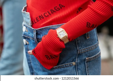 MILAN, ITALY - SEPTEMBER 22, 2018: Woman with red Balenciaga sweater, golden Cartier watch and blue denim trousers before Salvatore Ferragamo fashion show, Milan Fashion Week street style