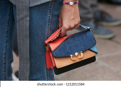MILAN, ITALY - SEPTEMBER 22, 2018: Woman with Paula Cademartori bag and blue denim trousers before Salvatore Ferragamo fashion show, Milan Fashion Week street style