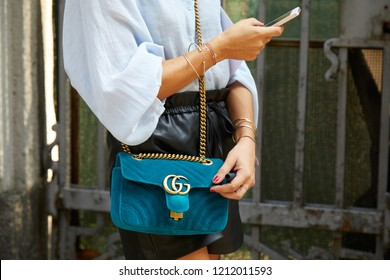 MILAN, ITALY - SEPTEMBER 22, 2018: Woman with blue velvet Gucci bag looking at smartphone before Simonetta Ravizza fashion show, Milan Fashion Week street style