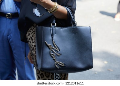 MILAN, ITALY - SEPTEMBER 22, 2018: Woman with black leather Karl Lagerfeld bag and golden bracelet before Simonetta Ravizza fashion show, Milan Fashion Week street style