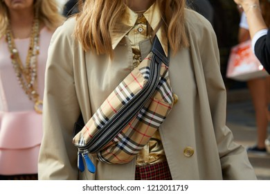 MILAN, ITALY - SEPTEMBER 22, 2018: Woman with Burberry pouch, beige coat and golden shirt before Gabriele Colangelo fashion show, Milan Fashion Week street style