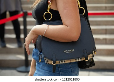 MILAN, ITALY - SEPTEMBER 22, 2018: Woman with Burberry bag and blue denim trousers before Gabriele Colangelo fashion show, Milan Fashion Week street style