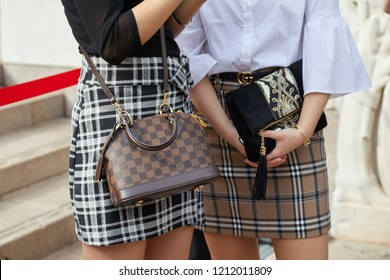 MILAN, ITALY - SEPTEMBER 22, 2018: Women with brown Louis Vuitton checkered bag and skirt before Gabriele Colangelo fashion show, Milan Fashion Week street style