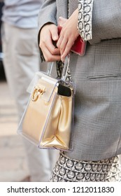 MILAN, ITALY - SEPTEMBER 22, 2018: Woman with Ferragamo golden and transparent plastic bag before Salvatore Ferragamo fashion show, Milan Fashion Week street style