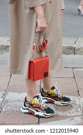 MILAN, ITALY - SEPTEMBER 22, 2018: Woman with red bag and beige trench coat before Salvatore Ferragamo fashion show, Milan Fashion Week street style
