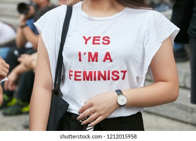 MILAN, ITALY - SEPTEMBER 22, 2018: Woman with white shirt with red feminist writing before Salvatore Ferragamo fashion show, Milan Fashion Week street style