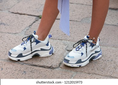 MILAN, ITALY - SEPTEMBER 22, 2018: Woman with white, blue and purple Balenciaga sneakers before Salvatore Ferragamo fashion show, Milan Fashion Week street style
