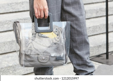 MILAN, ITALY - SEPTEMBER 22, 2018: Woman with gray, checkered trousers and gray leather Chanel bag in plastic transparent bag before Salvatore Ferragamo fashion show, Milan Fashion Week street style