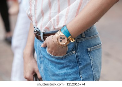 MILAN, ITALY - SEPTEMBER 22, 2018: Man with golden Michael Kors chronograph, blue denim trousers and white and pink striped shirt before Salvatore Ferragamo fashion show, Milan Fashion Week